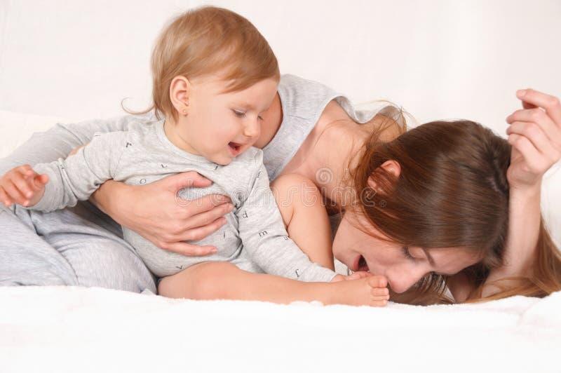 照顾与她的女儿的戏剧白色床背景的 免版税图库摄影