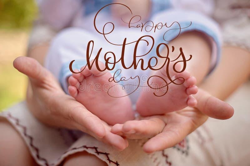 照顾举行她新出生的儿子和愉快的母亲节文本的脚 书法字法手凹道 免版税库存照片