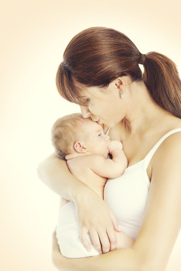 照顾亲吻新出生的婴孩,拿着和亲吻新出生的孩子的妈妈 免版税库存图片