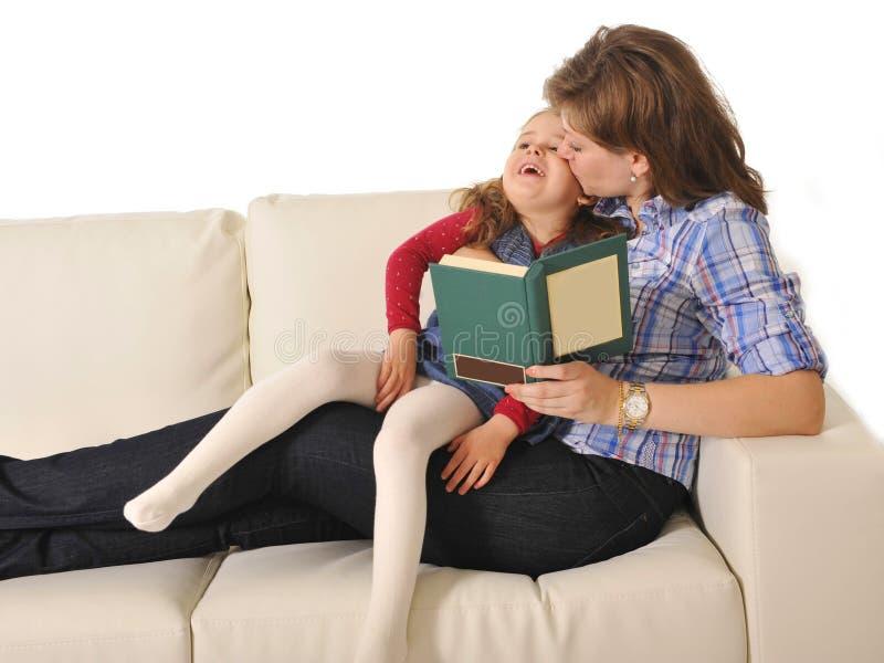 照顾亲吻和讲童话给逗人喜爱的矮小的女儿 库存照片