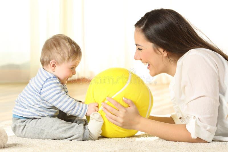 照顾使用与她的在地板上的婴孩 免版税库存图片