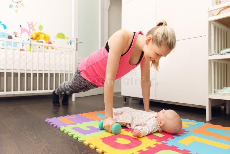 照顾做健身和使用与她的婴孩 库存图片