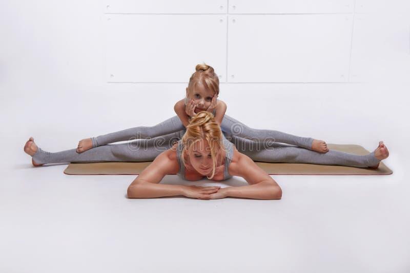 照顾做瑜伽锻炼,健身家庭体育,体育的女儿被配对的妇女坐分开舒展他的腿在d的地板 免版税库存照片