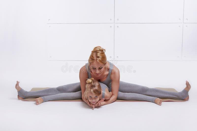 照顾做瑜伽锻炼,健身家庭体育,体育的女儿被配对的妇女坐分开舒展他的腿在d的地板 免版税库存图片