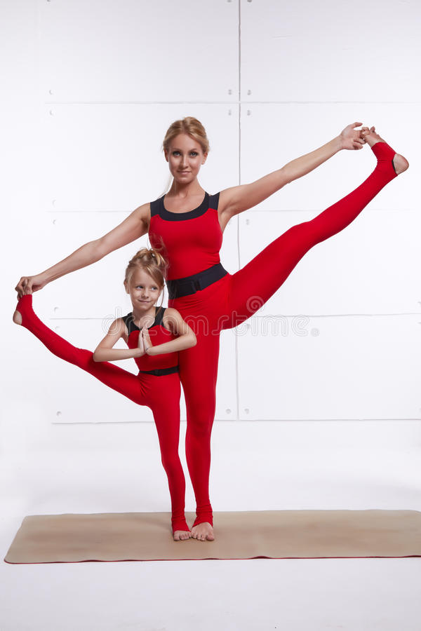 照顾做瑜伽锻炼,健身,健身房的女儿佩带同样舒适的田径服,家庭体育,被配对的体育 免版税库存照片