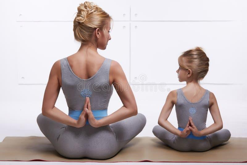 照顾做瑜伽锻炼,健身,健身房的女儿佩带同样舒适的田径服,家庭体育,被配对的体育 免版税库存图片