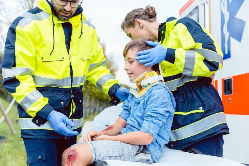 照顾受伤的男孩的紧急军医 免版税库存照片