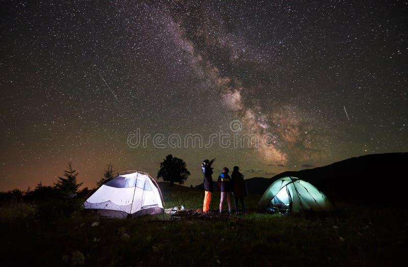 照顾和两个儿子远足者在充分野营在山在夜空下星和银河 图库摄影