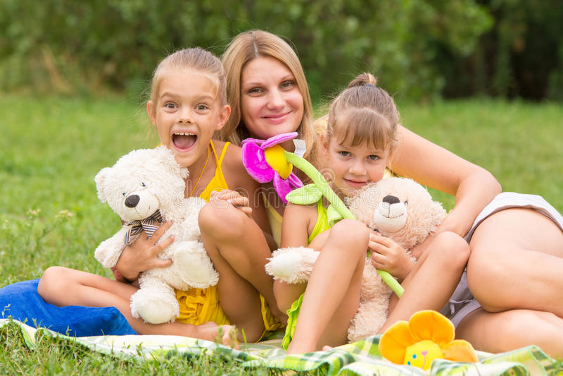照顾和两个女儿与软的玩具坐野餐 免版税库存照片