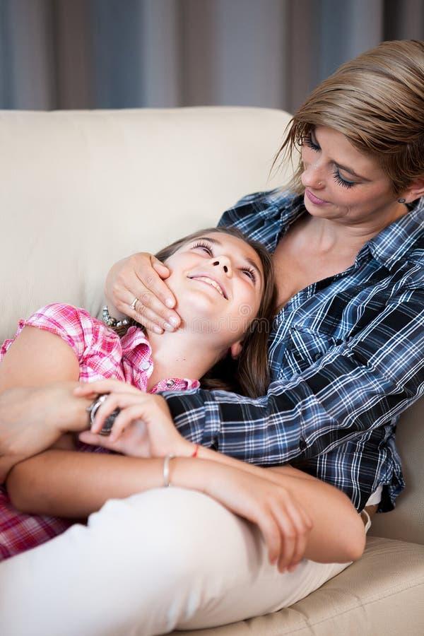 照顾和互相谈话她的漂亮的孩子的女儿,坐在客厅 库存照片