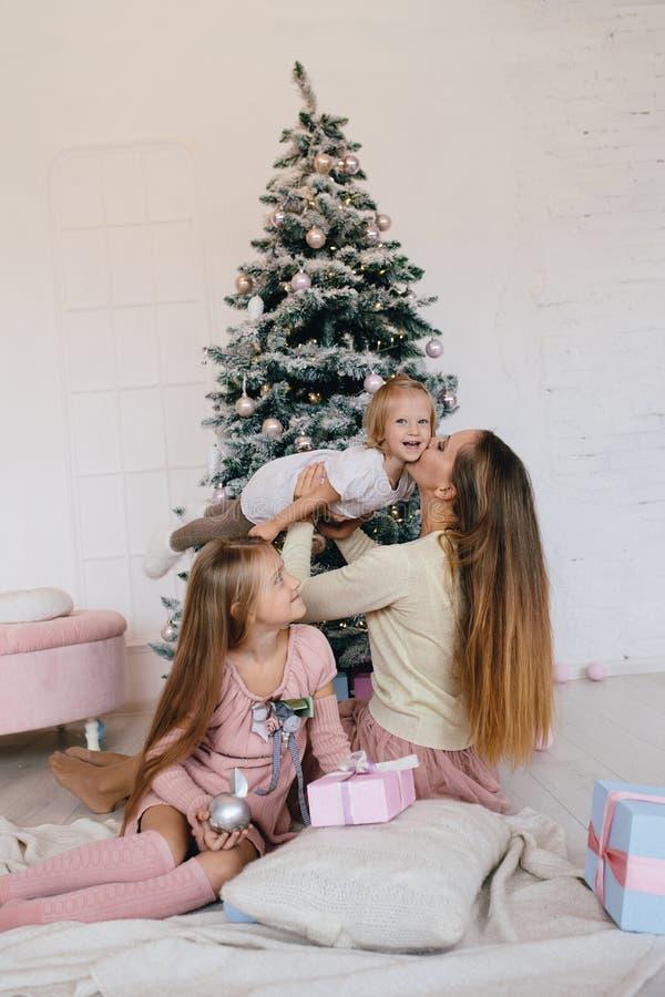 照顾和在家使用在近圣诞树的两个女儿 愉快的家庭获得乐趣为圣诞节假日 免版税图库摄影