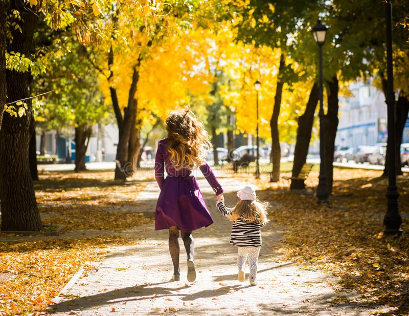 照顾和她的一起使用在秋天步行的儿童女孩本质上户外 图库摄影