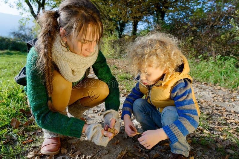 照顾和她的使用与秋叶的儿子 免版税图库摄影