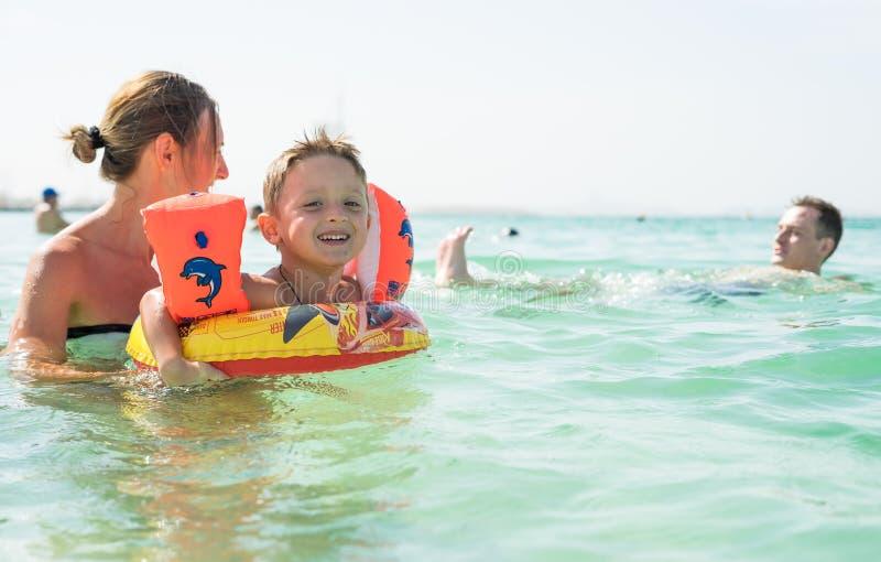 照顾和她的使用和跑在海滩的儿子 友好的家庭的概念 库存照片