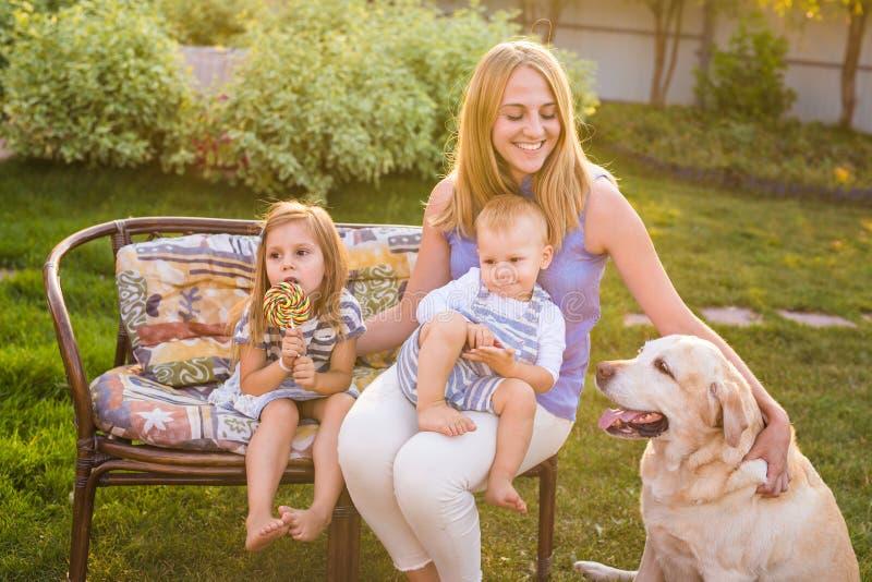 照顾和她的放松在有爱犬的庭院里的孩子 使用与他们的在a的拉布拉多猎犬狗的愉快的家庭 免版税图库摄影