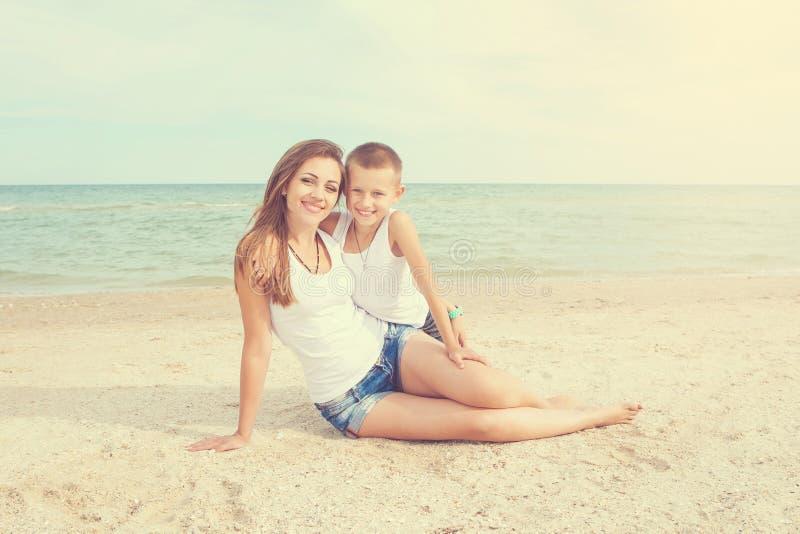 照顾和获得她的儿子在海滩的乐趣 免版税库存照片