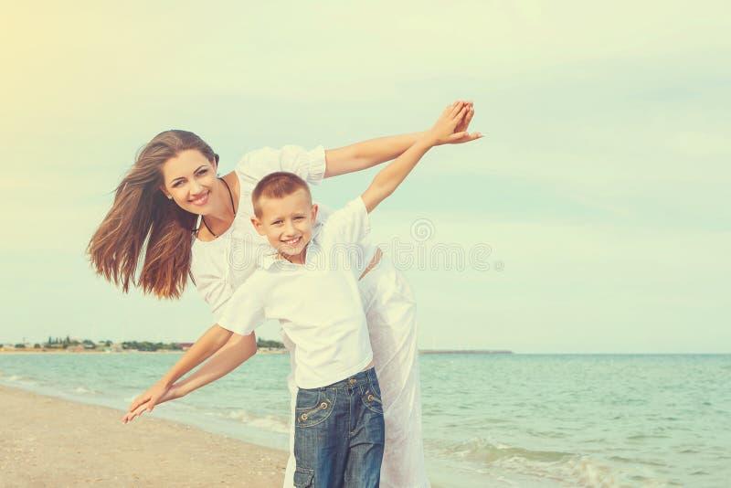 照顾和获得她的儿子在海滩的乐趣 库存图片
