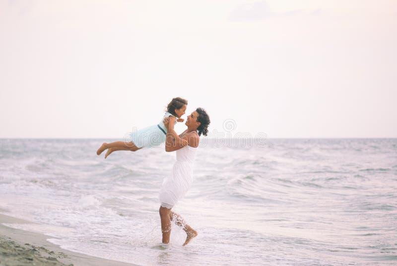 照顾和获得她的女儿在海滩的乐趣 免版税库存照片