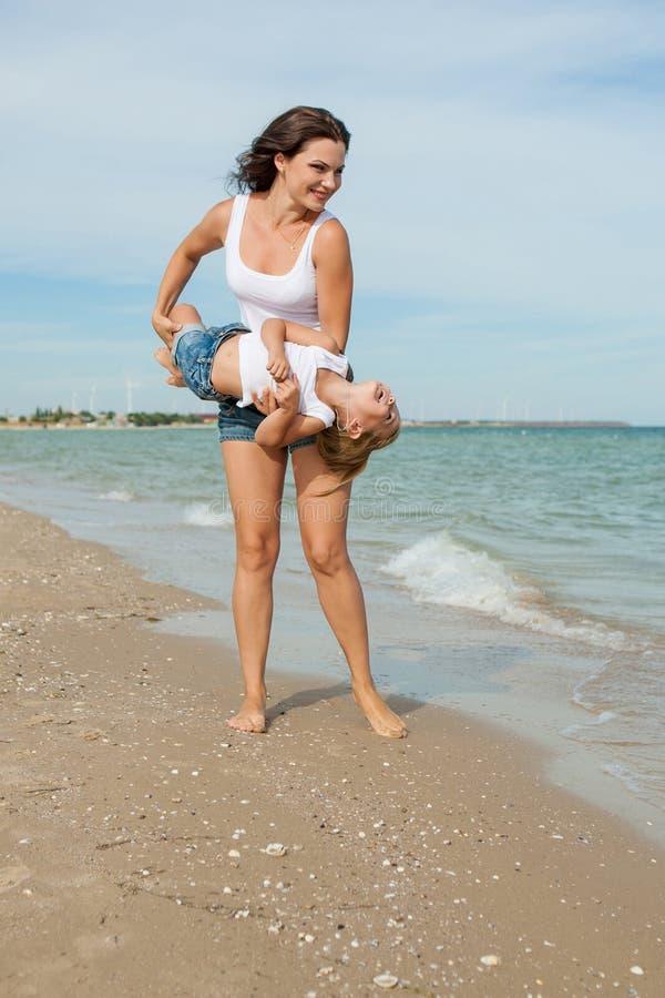 照顾和获得她的女儿在海滩的乐趣 免版税库存图片