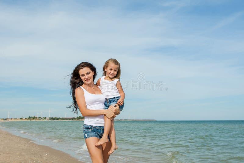 照顾和获得她的女儿在海滩的乐趣 库存图片