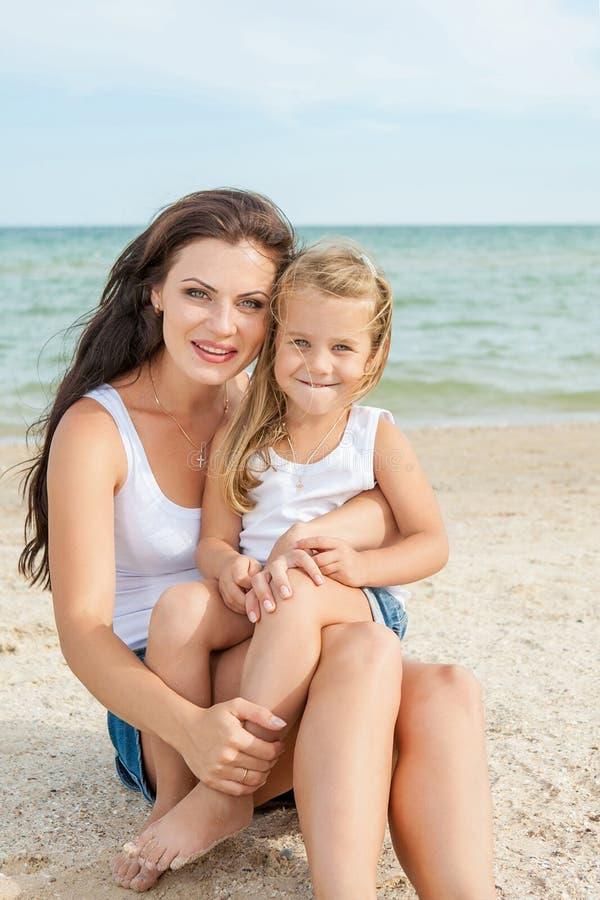 照顾和获得她的女儿在海滩的乐趣 库存照片