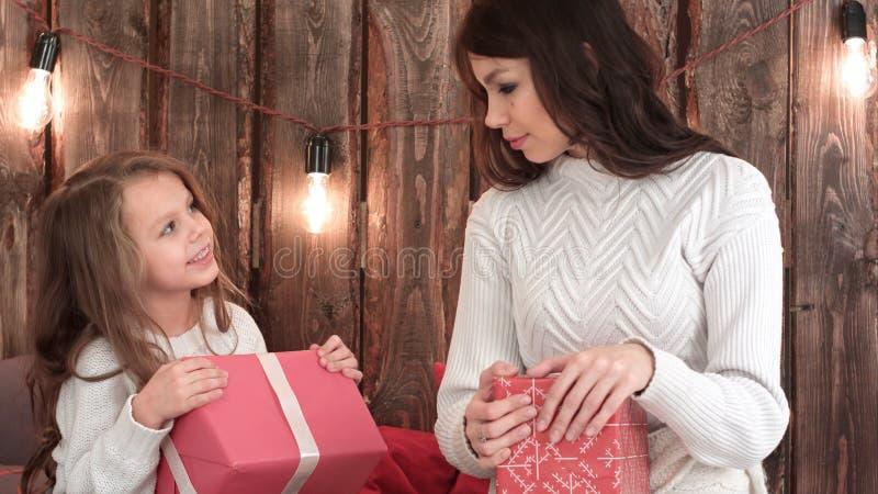 照顾和设法一个逗人喜爱的小女孩拿着Xmas礼物和猜测什么`里面s 库存照片