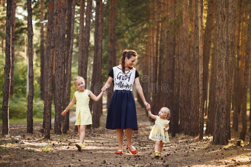 照顾和走在森林家庭en的两个小女儿 免版税库存照片