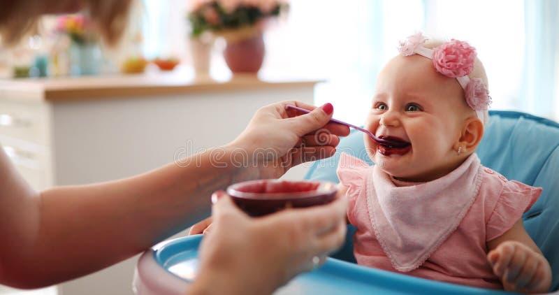 照顾喂养她的有匙子的女婴 免版税库存图片