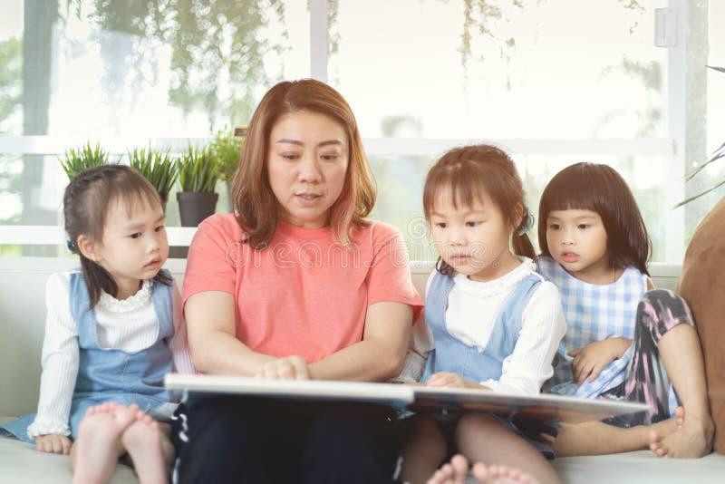 照顾在家读书给她的女儿 图库摄影