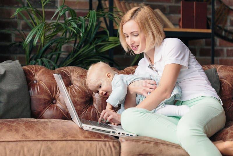 照顾坐沙发,当研究有婴孩的时膝上型计算机 免版税库存照片