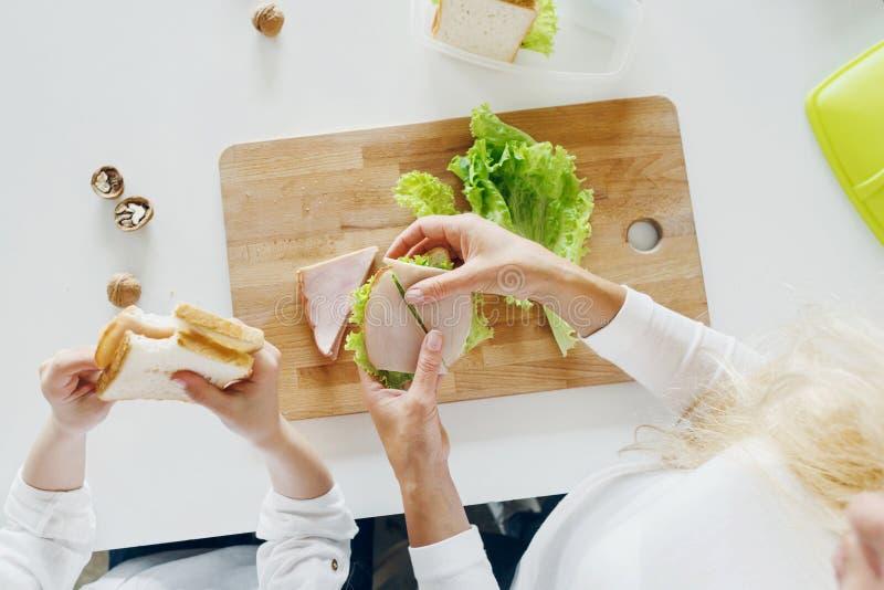 照顾女儿吃三明治在家厨房顶视图 库存照片