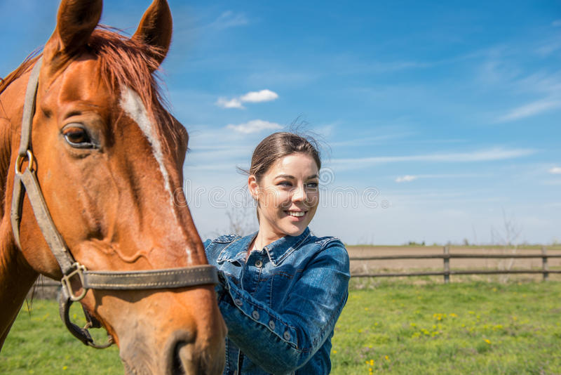 照顾她的棕色马的愉快的美丽的浅黑肤色的男人 免版税库存图片