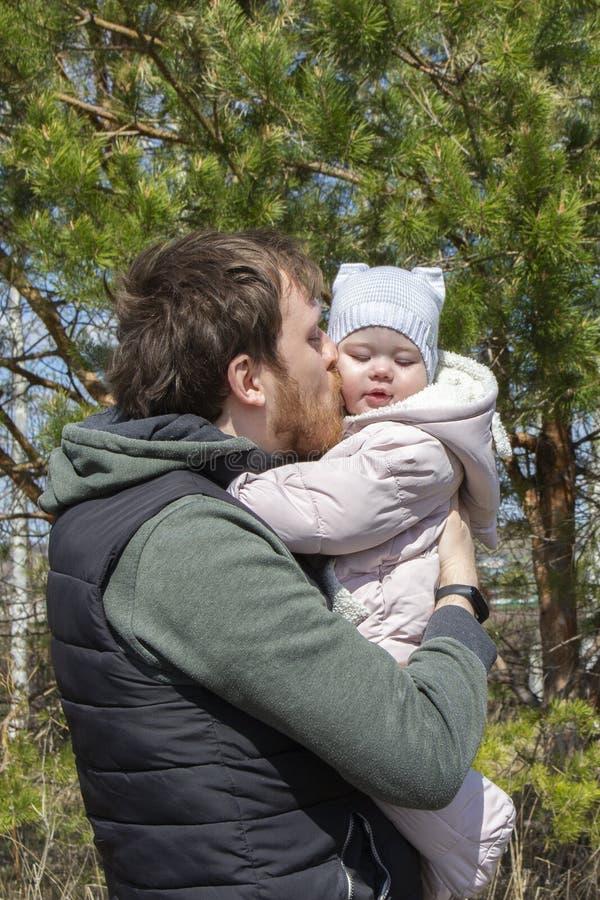 照顾孩子的柔软爱爸爸,并且女儿,年轻人在他的胳膊举行亲吻群衣服的女婴 免版税库存图片