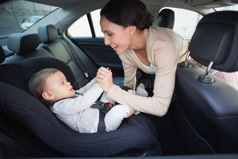 照顾巩固她的汽车座位的婴孩 免版税库存图片