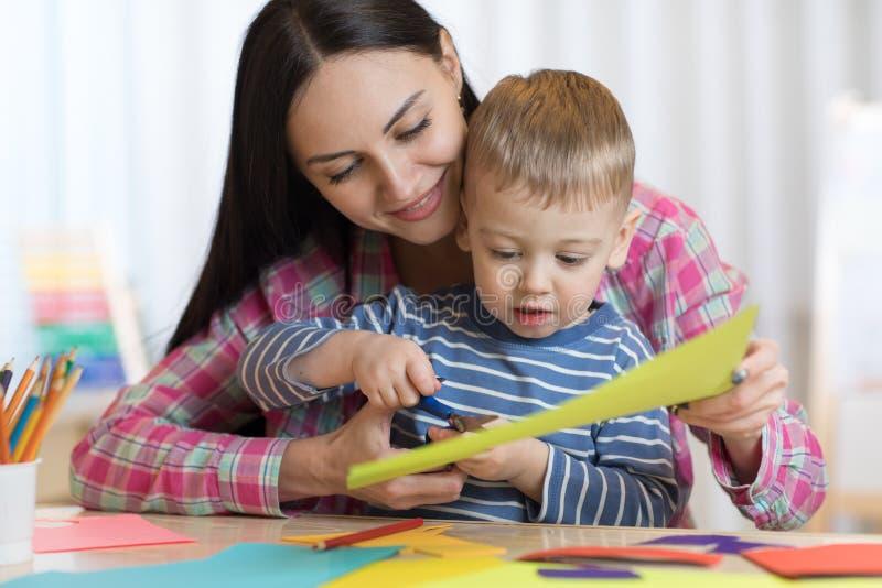 照顾帮助她的孩子切开色纸 免版税图库摄影