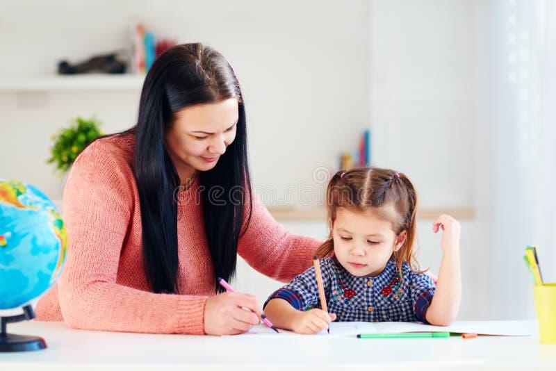 照顾帮助的女儿在家开发文字技能 免版税图库摄影