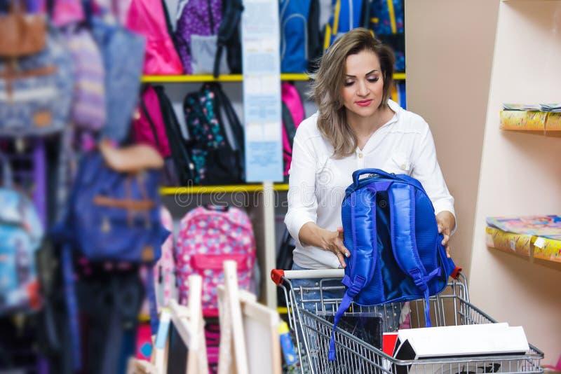 照顾愉快的蓝色白色购买书包购物中心少妇troley购物超级市场文具 免版税库存照片