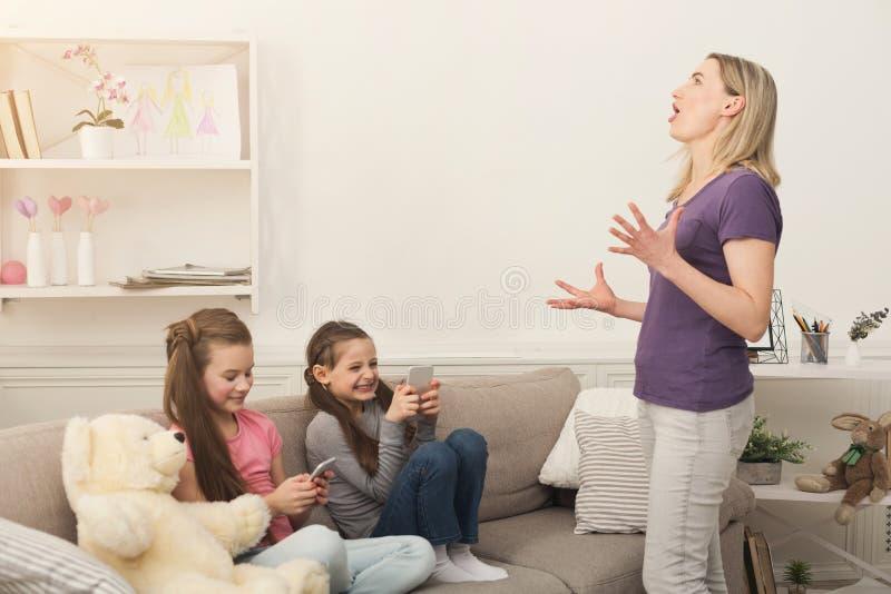 照顾感到恼怒,当使用手机时的小女孩 免版税图库摄影