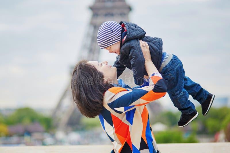 照顾投掷她的小儿子在天空中在埃佛尔铁塔附近 免版税库存照片