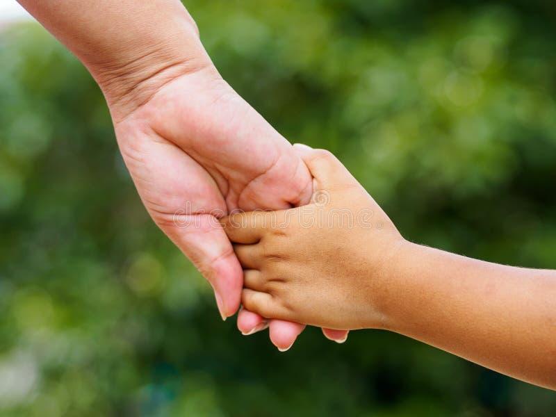 照顾握在bokeh背景的` s手一只小女孩` s手 库存图片