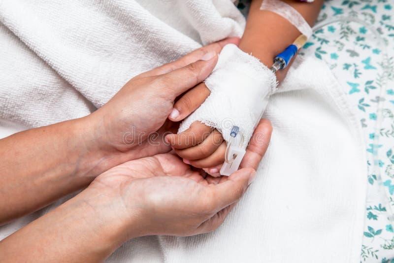 照顾握有IV解答的儿童的手 免版税图库摄影