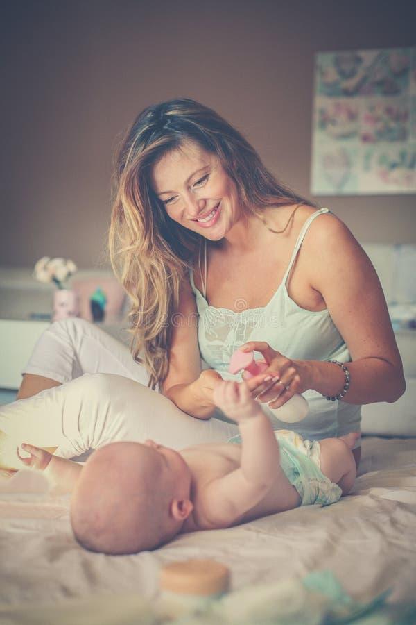照顾改变的尿布她的在床上的小婴孩 免版税库存照片