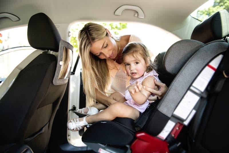 照顾放他的儿童女儿入她的在汽车的汽车座位 库存图片