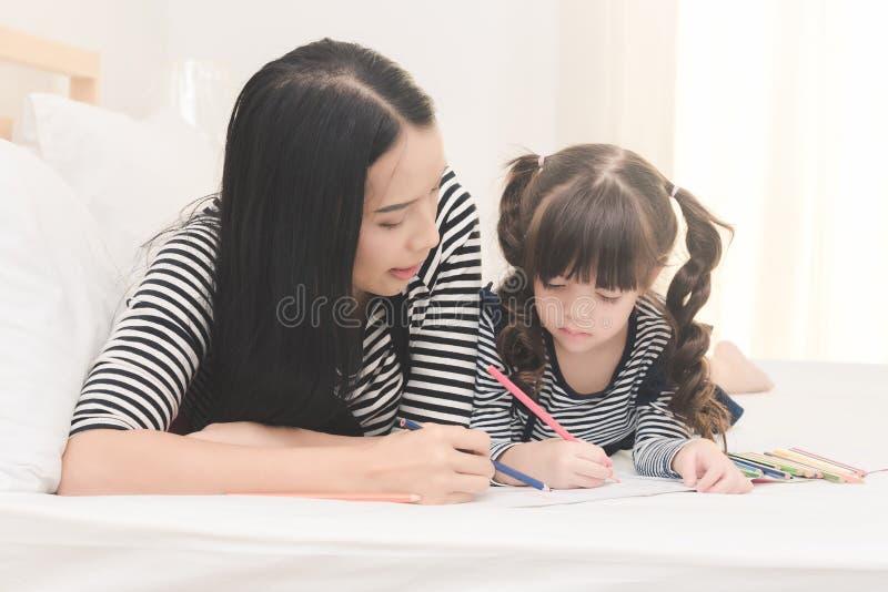 照顾教她的女儿孩子对在家学习 库存照片