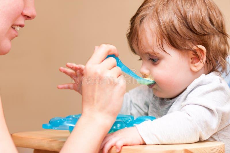照顾有匙子的哺养的婴孩在桌上 免版税图库摄影