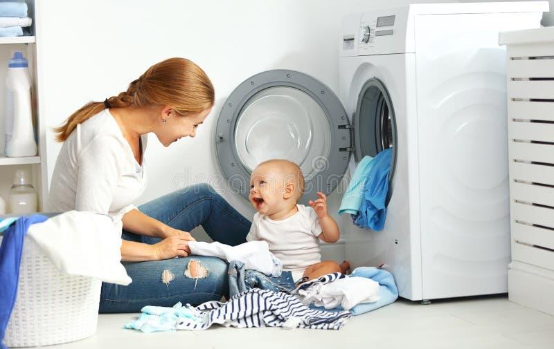 照顾有婴孩折叠衣裳的一位主妇入洗涤的ma 库存照片
