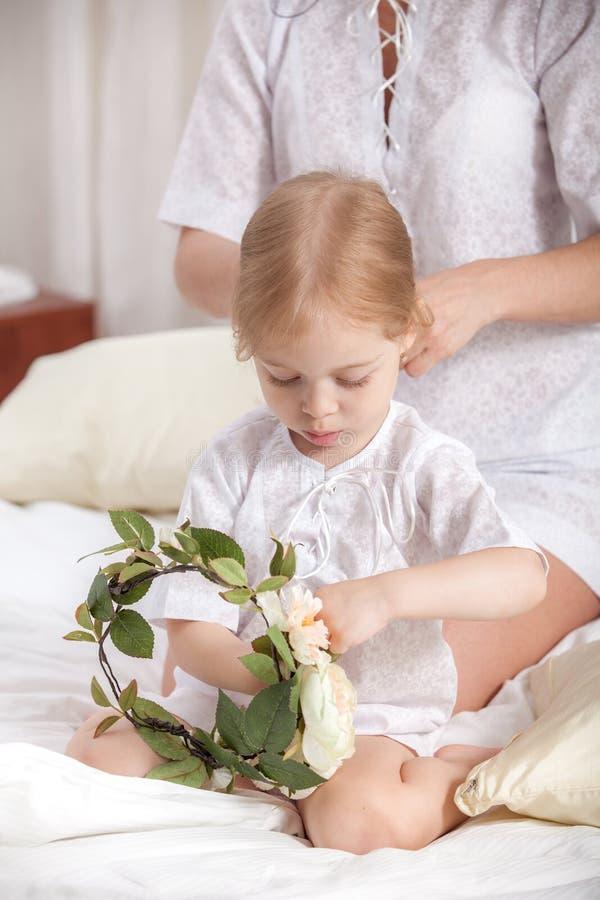 照顾梳子小女儿在床上 库存照片