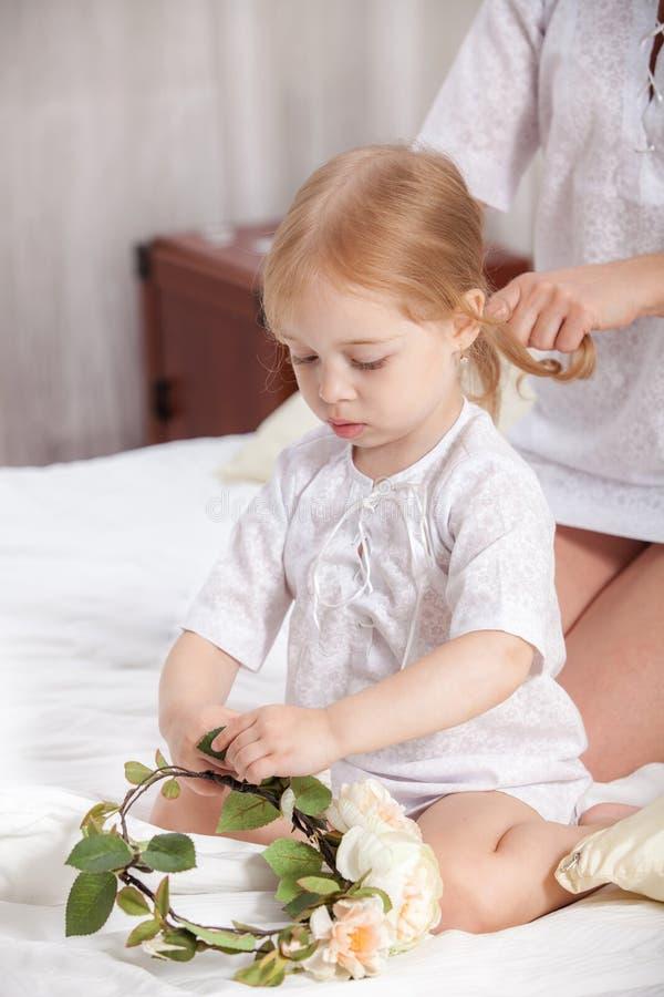 照顾梳子小女儿在床上 免版税库存图片