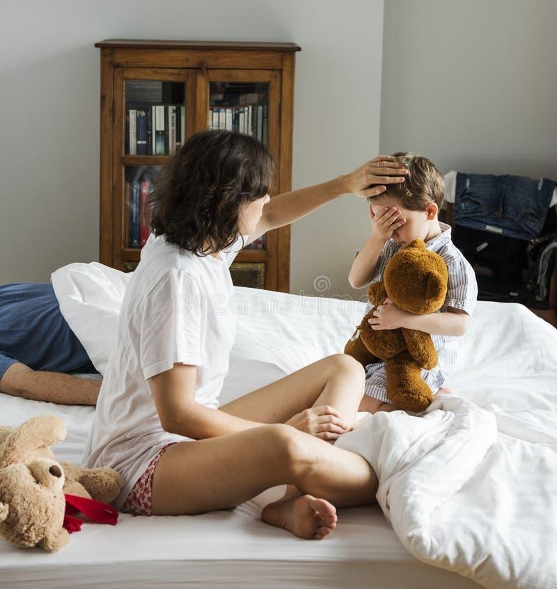 照顾照顾病的孩子在床上 图库摄影