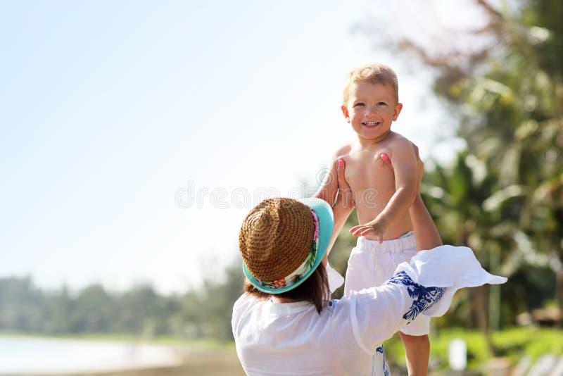 照顾获得在海滩的乐趣与她的小儿子 免版税库存照片